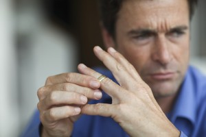 Mature man toying with gold wedding ring on finger Austin Divorce Attorney
